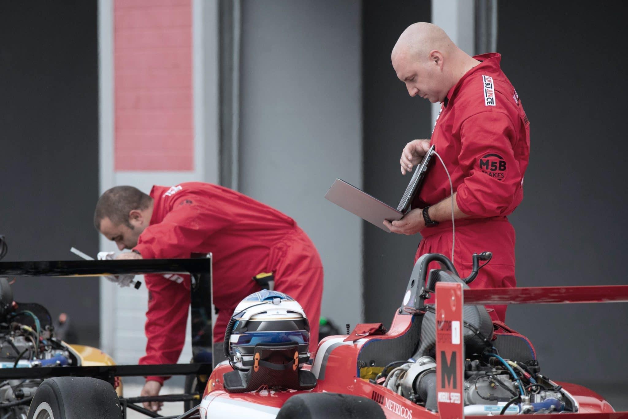 Pit crew member using laptop at pit stop.