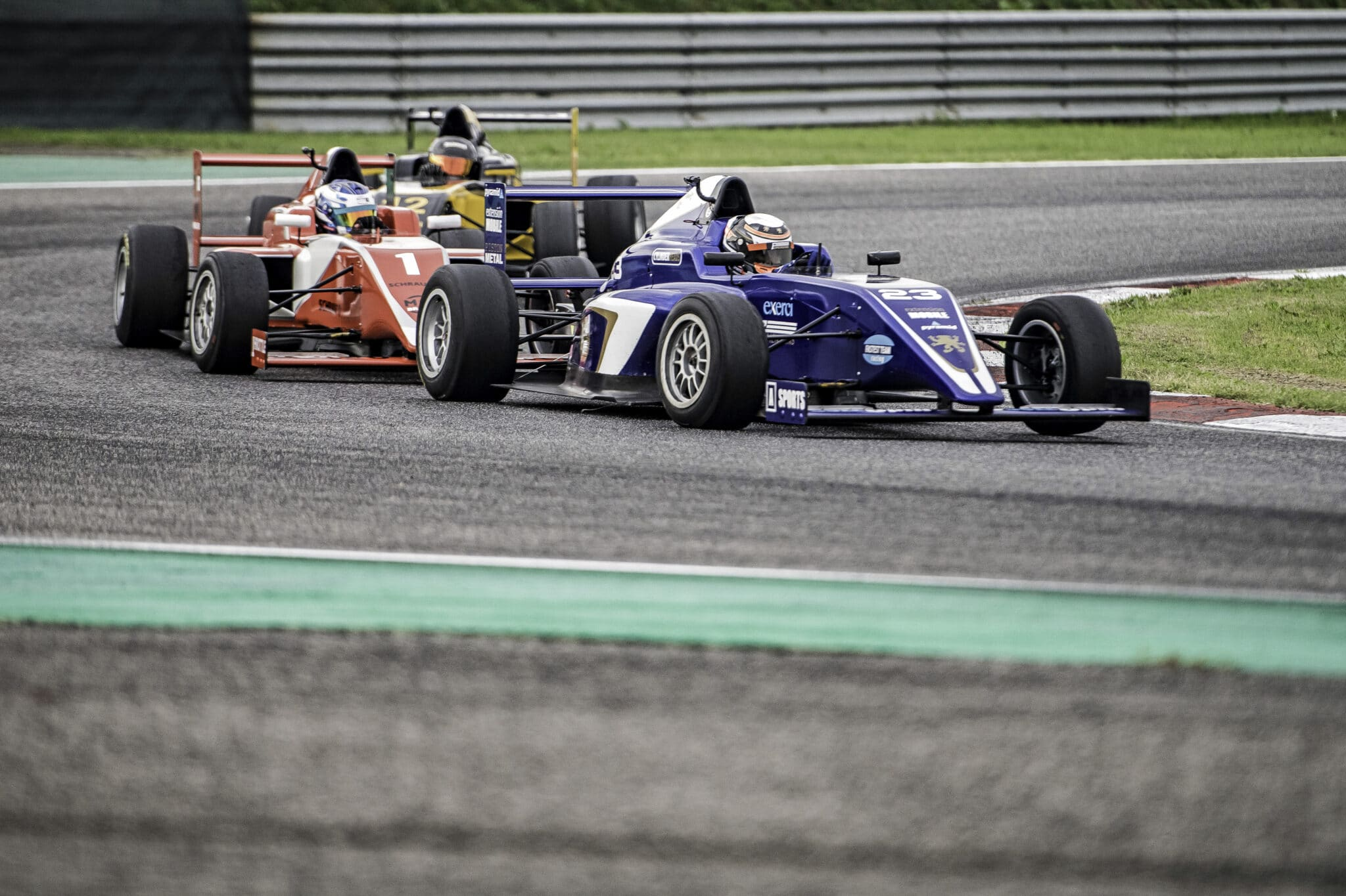 Three open-wheel formula race cars driving into a bend on a racing track.